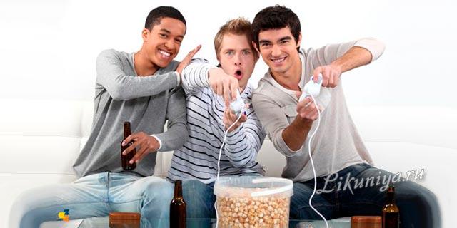 Молодые люди пьют пиво и играют в компьютерную игру