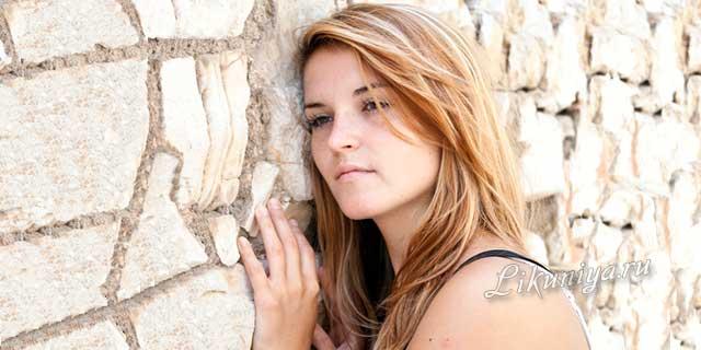 Девушка в раздумьях прислонилась к каменной стене