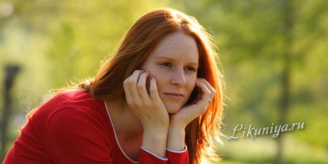 Рыжеволосая девушка сидит на скамейке